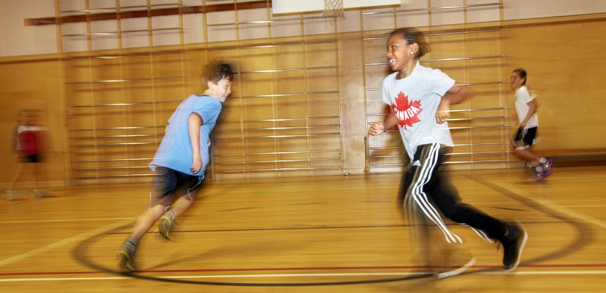 This image depicts a young boy and girl running in a circle in the gym